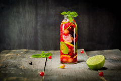 Bottle with detox water, berries and citrus inside. Dark background and old wooden table surface. Stock Photos