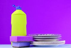 A bottle of dish washing, sponges, utensils on a wooden pastel color table against wall background, copy space. A bottle of dish washing, sponges, utensils on a royalty free stock images