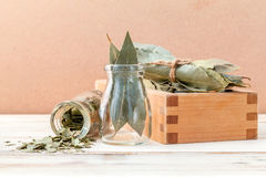Bottle of dried bay leaves and wooden box with selective focus o Stock Photography