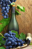Bottle, drinking horn and bunch of grapes Stock Image