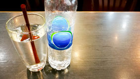 Bottle drinking water and a glass of water with brown straw royalty free stock photography