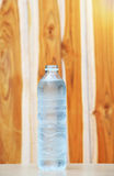 A bottle of Drinking water. On wooden background Royalty Free Stock Photos