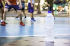 Bottle of drinking water on the wooden chair Background Blurry image of people playing basketball on a court royalty free stock photography
