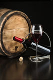 Bottle of dry red wine with a glass. On a background the barrel Royalty Free Stock Images
