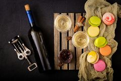 Bottle of dry white wine and a macaroon. Royalty Free Stock Image