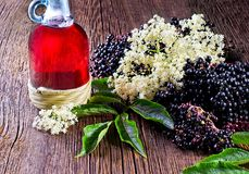 Bottle with elderberry juice and fresh berry fruits on wooden table. Stock Photos
