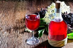 Bottle with elderberry juice and fresh berry fruits on wooden table. Royalty Free Stock Photos