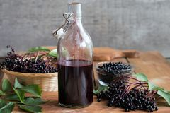 A bottle of elderberry syrup on a wooden background. A bottle of homemade elderberry syrup on a wooden table, with fresh elderberries in the background Stock Photos