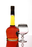 Bottle elite cognac and empty goblet Stock Photo