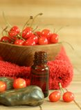 Bottle of essence oil, fresh cherry and red towel Stock Images