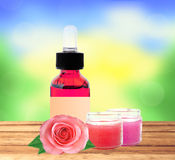 Bottle with essence oil and rose flowers on wooden table over na Stock Photography