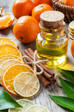 Bottle of essential citrus oil, dried orange and lemon slice. S, cinnamon sticks and ripe tangerines on old table Stock Photo