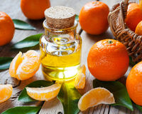 Bottle of essential citrus oil and ripe tangerines with leaves. On old wooden kitchen table Stock Image