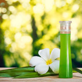 Bottle of essential fragrant oil on wooden floor with pandan leaf and flower. Royalty Free Stock Photography
