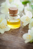 Bottle of essential jasmine oil and jasmin flowers. Royalty Free Stock Photos