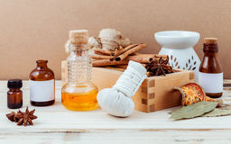 Bottle of essential oil for ayurveda massage with cinnamon stick. Star anise ,bay leaves ginger root and herbal compress ball with selective focus on shabby royalty free stock photo