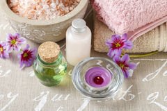 Bottle of essential oil, bowl with sea salt and scented candle. Spa time Royalty Free Stock Photo