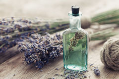 Bottle of essential oil and bunch of lavender flowers. stock photo