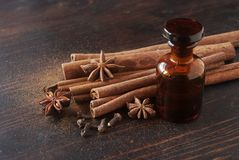 Bottle of essential oil Cinnamon. Bottle of essential oil, Cinnamon sticks, carnation and anise close up on wooden table. Selective focus stock image