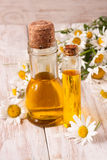 bottle with essential oil and fresh chamomile flowers on a light wooden background stock photography