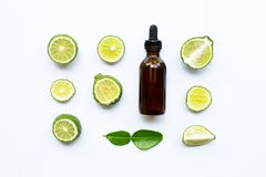 Bottle of essential oil and fresh kaffir lime or bergamot fruit isolated on white. Background royalty free stock images