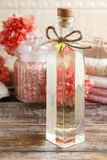 Bottle of essential oil and jar of sea salt on wooden table. Stock Image