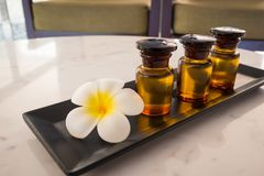 Bottle of essential oil and jasmin flower with plumeria flower setup on marble table. For spa relaxing massage at thailand stock photos