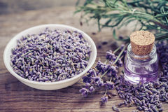 Bottle of essential oil and lavender flowers in bowl. And on table. Selective focus Royalty Free Stock Image
