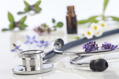 Bottle of essential oil with medicinal plant and stethoscope royalty free stock photo