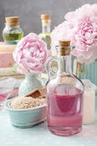 Bottle of essential oil and peonies in the background Royalty Free Stock Images