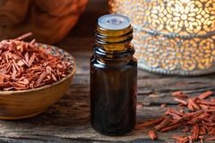 A bottle of sandalwood essential oil with pieces of red sandalwood stock image