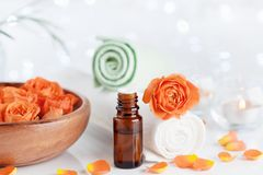 Bottle with essential oil from rose flowers on white table. Spa, aromatherapy, wellness, beauty background. Stock Photo
