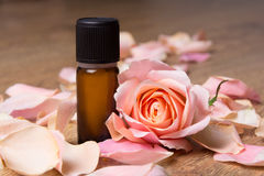 Bottle with essential oil and rose petals. On wooden background stock photography