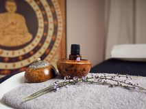 Bottle of essential oil in a round bowl of wood, next to a lavender branch, both arranged on a gray, rectangular terry towel, at stock photo