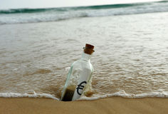 Bottle with euro sign on the sand of the beach Royalty Free Stock Photos