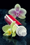 Bottle of face cream/lotion with orchid flowers Stock Photos