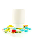 Bottle with falling out pills. Bottle with falling out many-coloured pills on white background Stock Photos