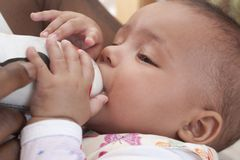 Bottle feeding. Father feeding her 3 months old baby girl with formula powder Stock Photo