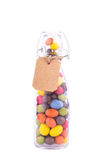 Bottle filled with candy colored glaze and price tag or label fr. Om paper on twine cord, isolated Stock Photos