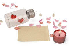 A bottle filled with heart and petals and paper on white backgro. Und Stock Images