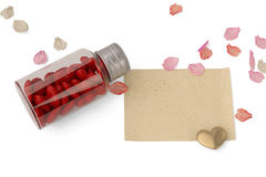 A bottle filled with heart and petals and paper on white backgro. Und Stock Photography