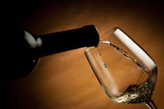Bottle filling the glass of wine. Splash of delicious flavor Royalty Free Stock Photography