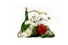 Bottle and flowers. Arrangement from artificial colors, red pepper and a bottle stock photos