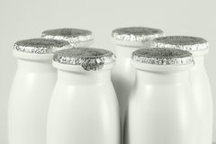 Bottle with foil cap with yogurt. White plastic bottle with foil cap with yogurt, halfbody Royalty Free Stock Photo
