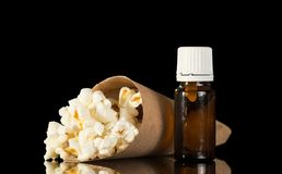 Bottle with fragrant liquid for inhaling steam and packet with popcorn isolated on black Stock Image