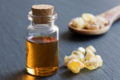 A bottle of frankincense essential oil with frankincense crystal. A bottle of frankincense essential oil with frankincense resin crystals in the background Royalty Free Stock Images