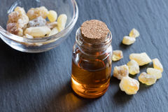 A bottle of frankincense essential oil with frankincense crystal. A bottle of frankincense essential oil with frankincense resin crystals in the background Stock Image