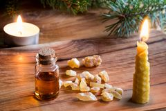 A bottle of frankincense essential oil with frankincense resin c. A bottle of frankincense essential oil with frankincense resin, a candle made from beeswax, and Royalty Free Stock Image