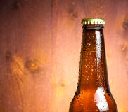 Bottle of fresh beer with drops on wood Stock Photos