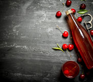 Bottle of fresh cherry juice with the leaves around. Stock Photography